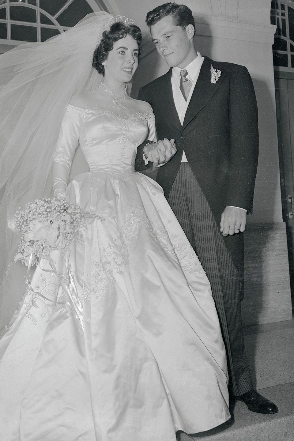 """<p>Liz was married eight times to seven husbands — but her first time down the aisle was with Conrad """"Nicky"""" Hilton when she was 18. She wore a satin long-sleeved gown with a silk gauze off-the-shoulder illusion neckline that was designed by MGM costume designer Helen Rose.</p><p><strong>RELATED</strong>: <a href=""""https://www.goodhousekeeping.com/life/entertainment/g2632/rare-photos-elizabeth-taylor/"""" rel=""""nofollow noopener"""" target=""""_blank"""" data-ylk=""""slk:60 Rare Photos of Elizabeth Taylor Through the Years"""" class=""""link rapid-noclick-resp"""">60 Rare Photos of Elizabeth Taylor Through the Years</a></p>"""