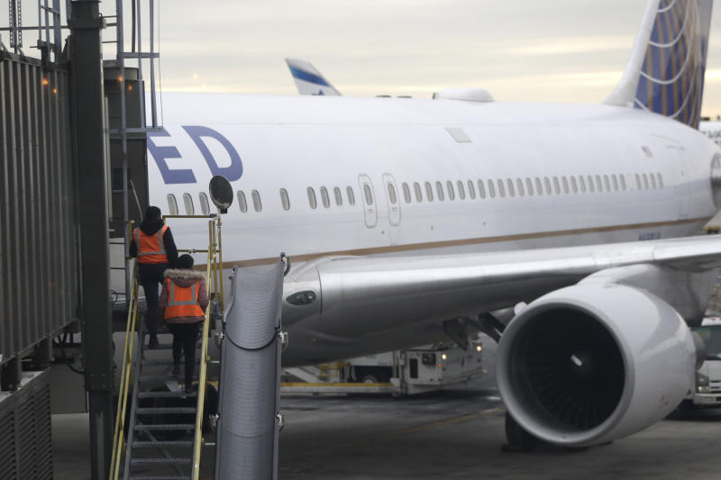 In this Jan. 23, 2019, photo employees walk up a ramp toward a ramp where a United Airlines jet is parked at a gate Newark Liberty International Airport in Newark, N.J. United Airlines reports financial results on Tuesday, July 16. (AP Photo/Julio Cortez)