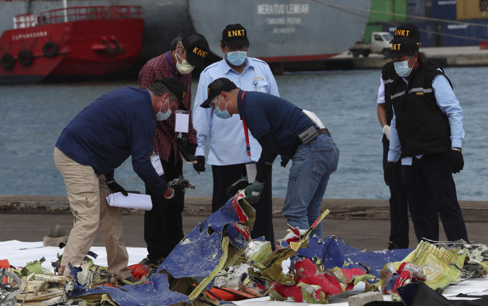 Members of the Indonesia's National Transportation Safety Committee (KNKT) and U.S. National Transportation Safety Board (NTSB) investigators team inspect debris found in the waters around the location where a Sriwijaya Air passenger jet crashed, at the search and rescue command center at Tanjung Priok Port in Jakarta, Indonesia, Saturday, Jan 16, 2021. (AP Photo/Achmad Ibrahim)