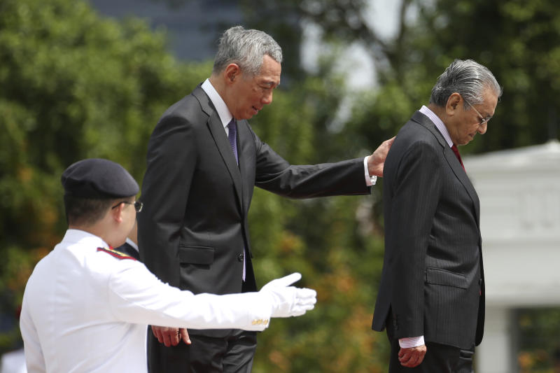 Malaysia's Prime Minister Mahathir Mohamad, right, inspects an honor guard with Singapore's Prime Minister Lee Hsien Loong during a visit at the Istana in Singapore, Monday, Nov. 12, 2018. (Feline Lim/Pool Photo via AP)