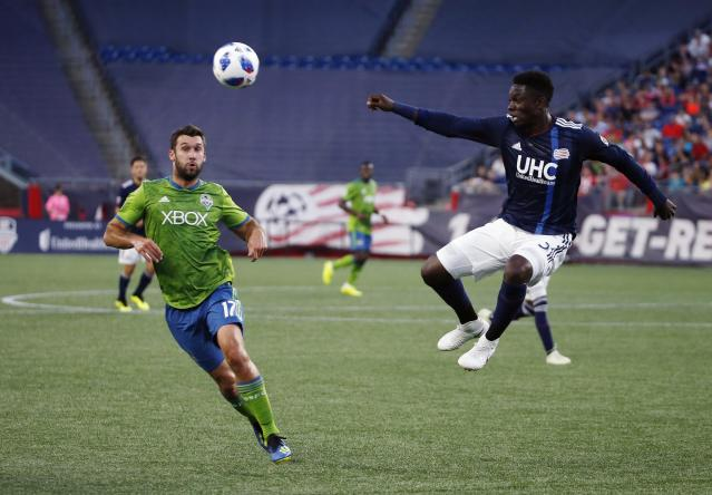 New England Revolution's Jalil Anibaba, right, sends the ball past Seattle Sounders' Will Bruin (17) during the first half of an MLS soccer game in Foxborough, Mass., Saturday, July 7, 2018. (AP Photo/Michael Dwyer)