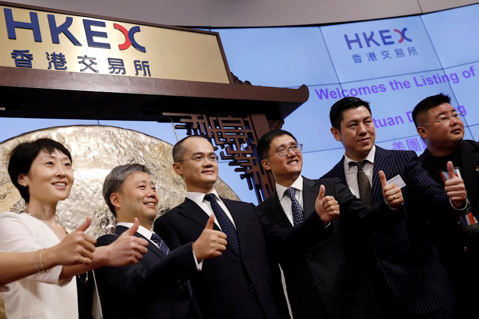 Wang Xing (3rd L), co-founder, chairman and chief executive officer of China's Meituan Dianping, attends the debut of the company at the Hong Kong Exchanges in Hong Kong, China, September 20, 2018. REUTERS/Tyrone Siu