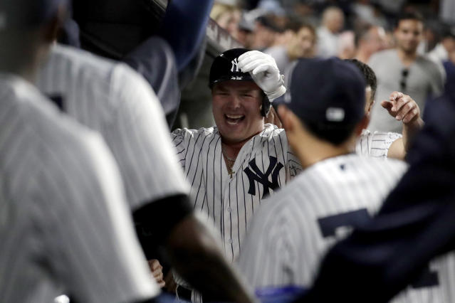 New York Yankees' Luke Voit, center, is congratulated in the dugout after hitting a solo home run off Boston Red Sox starting pitcher David Price during the fourth inning of a baseball game Wednesday, Sept. 19, 2018, in New York. (AP Photo/Julio Cortez)