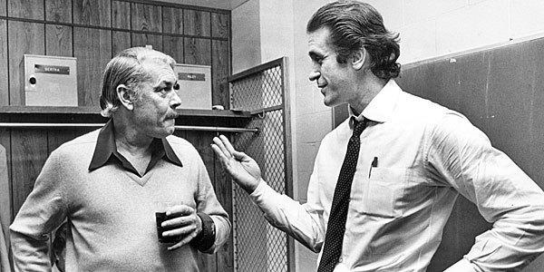 Lakers owner Jerry Buss talks with coach Pat Riley in Lakers locker room following a game.