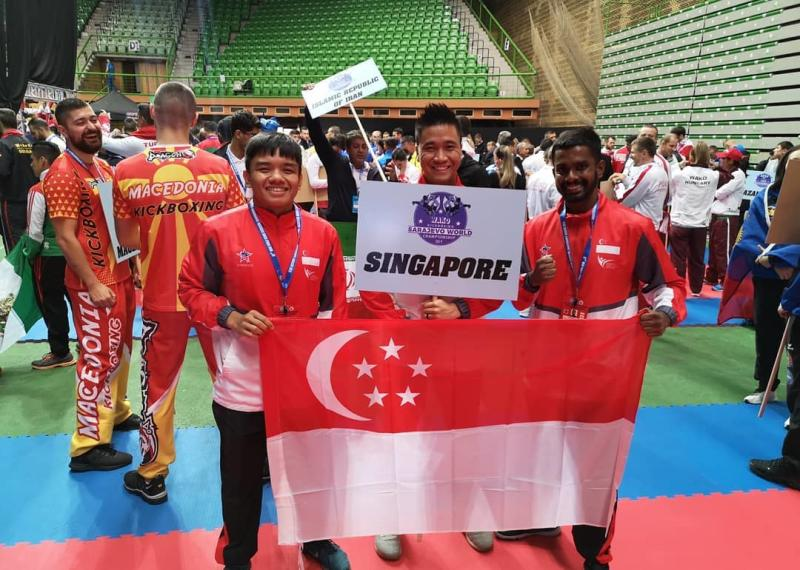Singapore athletes Nazri Sutari (left) and Abdul Rahman (right) at the World Kickboxing Championships with Joel Lye, vice-president of the Kickboxing Federation of Singapore. (PHOTO: Kickboxing Federation of Singapore)