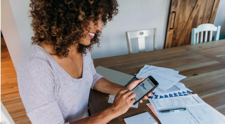 Woman using her mobile trading app