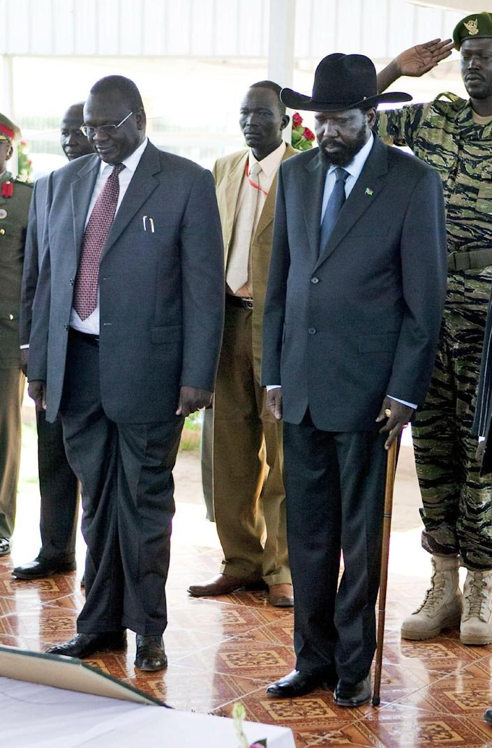 FILE--- In this file photo of Friday, May 21, 2010 file photo Government of South Sudan Vice President ,Riek Machar, front left, and President Salva Kiir, of South Sudan pay respects at the grave of late southern Sudanese rebel leader Dr. John Garang in Juba. Sporadic gunfire rang out early Monday, Dec. 16, 2013, in the South Sudan capital, Juba, in what a senior military official said were clashes between factions of the country's military. There has been political tension in the world's youngest nation since South Sudan President Kiir sacked Riek Machar as his deputy in July. The local Sudan Tribune newspaper reported on its website that clashes erupted late Sunday between members of the presidential guard in fighting that seemed to pit soldiers from Kiira's Dinka tribe against those from the Nuer tribe of Machar. (AP Photo/Pete Muller-File)