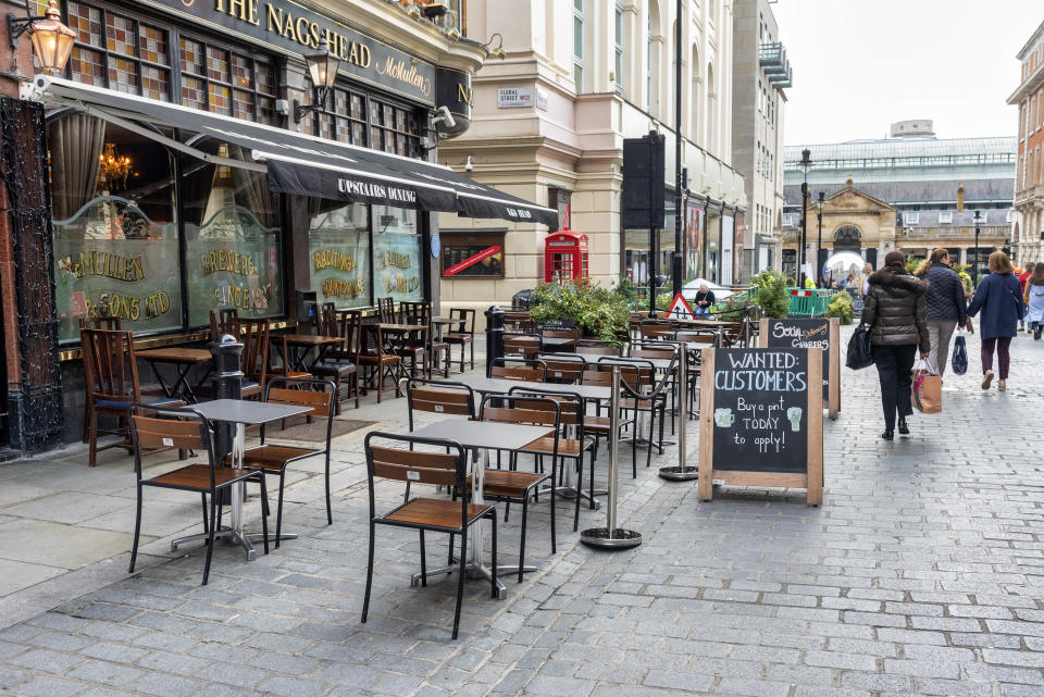 Empty tables are seen outside the The Nags Head pub