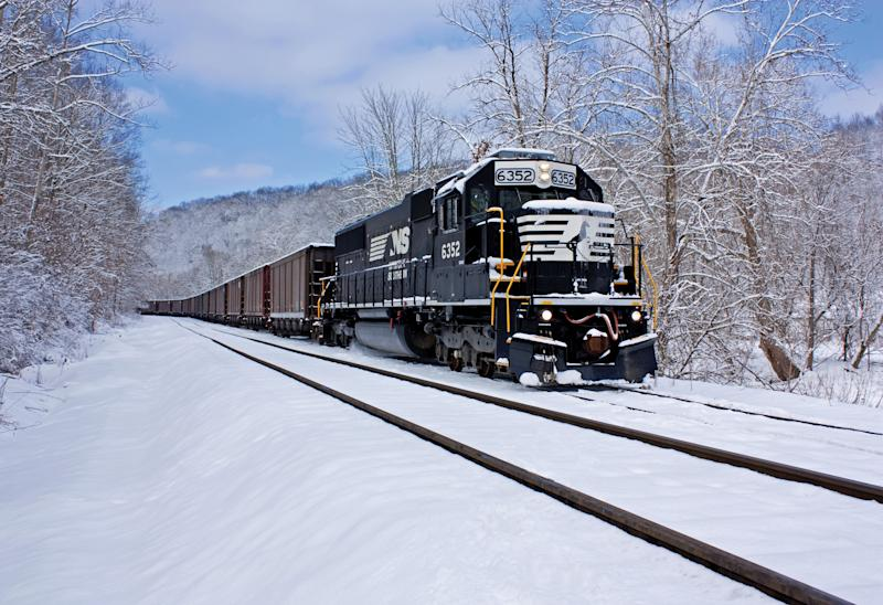 A Norfolk Southern locomotive engine pulls a train through snow.