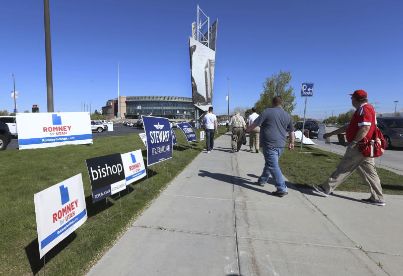 People walk to the Maverick Center to attend the Utah Republican 2018 nominating convention Saturday, April 21, 2018, in West Valley City, Utah. Mitt Romney is facing nearly a dozen Republican contenders in Utah on Saturday as he works to secure the state GOP nomination for a Senate seat without a primary. (AP Photo/George Frey)