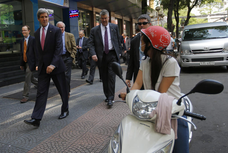 U.S. Secretary of State John Kerry, left, walks along a street in Ho Chi Minh City, Vietnam, to attend a service at the Notre Dame Cathedral Saturday, Dec. 14, 2013. Forty-four years after first setting foot in Vietnam as a young naval officer, Kerry returned once more, this time as America's top diplomat. (AP Photo/Brian Snyder, Pool)