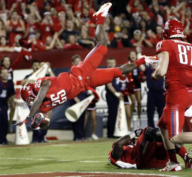 FILE - In this Nov. 23, 2012 file photo, Arizona's Ka'Deem Carey (25) jumps into the end zone for a touchdown as teammate Drew Robinson (87) watches during the first half of an NCAA college football game against Arizona State in Tucson, Ariz. Carey, Alabama linebacker C.J. Mosley, and Arizona State defensive tackle Will Sutton have been selected to The Associated Press All-America team for the second straight season, Tuesday, Dec. 17, 2013. (AP Photo/Wily Low, File)