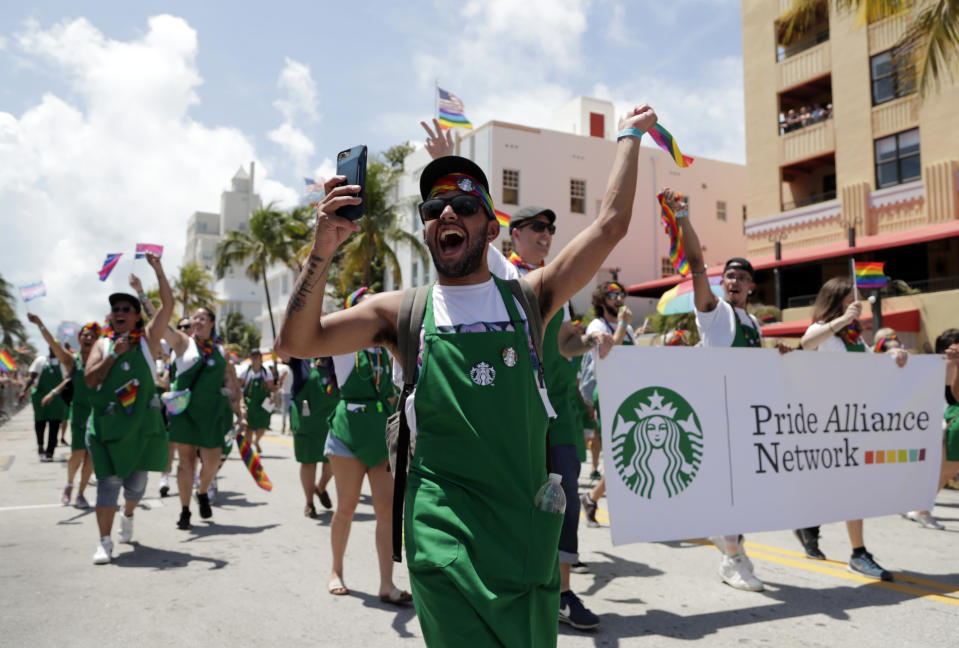 In this April 7, 2019, photo, people with the Pride Alliance Network, sponsored by Starbucks, walk along Ocean Drive, during the 11th annual Pride Parade, as part of Miami Beach Pride week, in Miami Beach, Fla. Florida is now home to two metro areas with among the highest concentrations of gay and lesbian coupled households in the U.S., according to a new report released by the U.S. Census Bureau. Orlando and Miami had the fourth and sixth highest concentrations of same sex coupled households in the U.S. (AP Photo/Lynne Sladky)