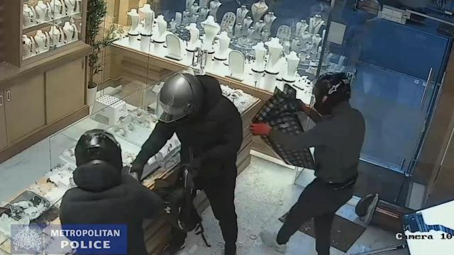 Video grab of members of the gang taking jewellery from the jewellery cases (SWNS)