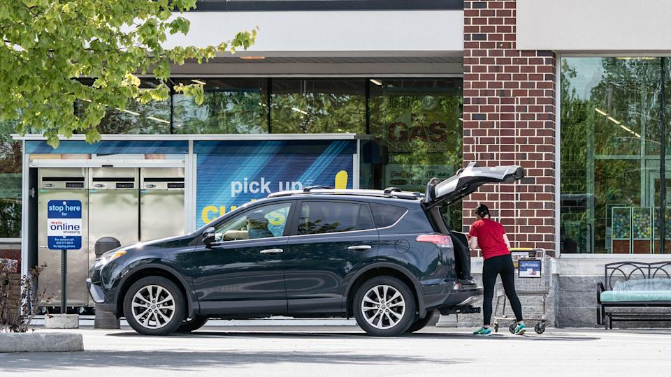Berks County, Pennsylvania, USA - May 19, 2020: Employee puts groceries in customers car at Weis Markets curb side pick-up.