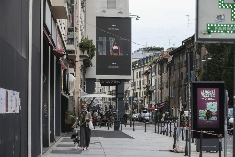 People walk past a giant screen streaming Versace fashion live show, during the Milan's fashion week in Milan, Italy, Friday, Sept. 25, 2020. (AP Photo/Luca Bruno)