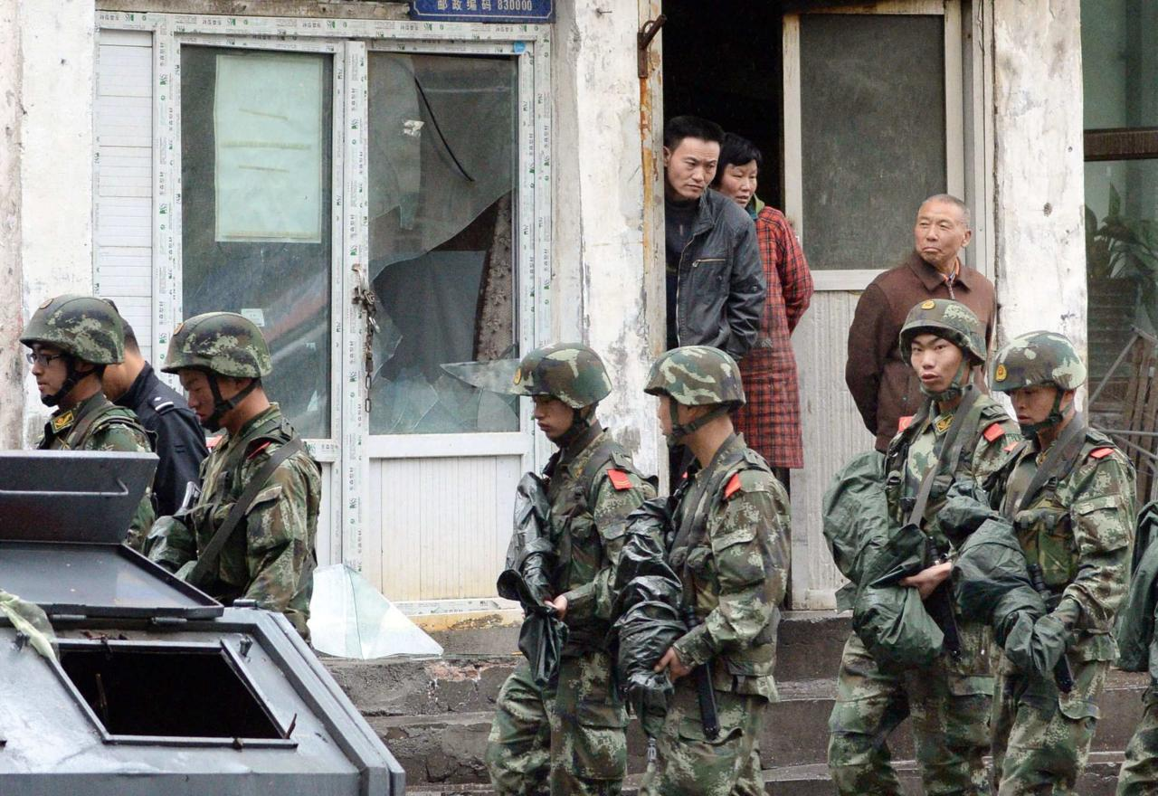 Paramilitary policemen patrol past a building, where a window was damaged by an explosion in Urumqi on Thursday, in the Xinjiang Uighur Autonomous Region, in this photo taken by Kyodo on May 22, 2014. Five suicide bombers carried out the attack which killed 31 people in the capital of China's troubled Xinjiang region, state media reported a day after the deadliest terrorist attack to date in the region. Picture taken May 22, 2014. Mandatory credit REUTERS/Kyodo (CHINA - Tags: CRIME LAW CIVIL UNREST) ATTENTION EDITORS - THIS IMAGE HAS BEEN SUPPLIED BY A THIRD PARTY. FOR EDITORIAL USE ONLY. NOT FOR SALE FOR MARKETING OR ADVERTISING CAMPAIGNS. MANDATORY CREDIT. JAPAN OUT. NO COMMERCIAL OR EDITORIAL SALES IN JAPAN. THIS PICTURE IS DISTRIBUTED EXACTLY AS RECEIVED BY REUTERS, AS A SERVICE TO CLIENTS. YES