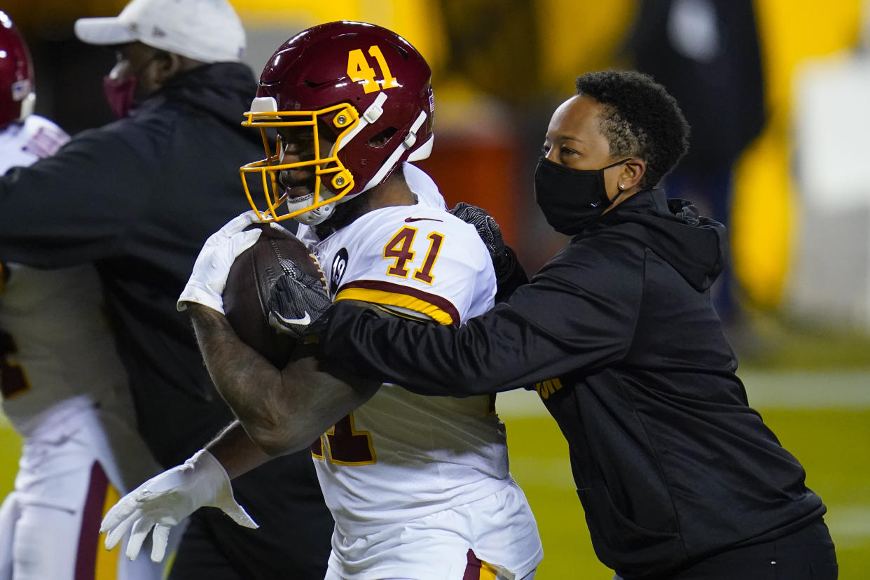 Full-year coaching intern Jennifer King, right, works with Washington Football Team running back J.D. McKissic (41) before the team's NFL wild-card playoff football game against the Tampa Bay Buccaneers, Saturday, Jan. 9, 2021, in Landover, Md. (AP Photo/Julio Cortez)