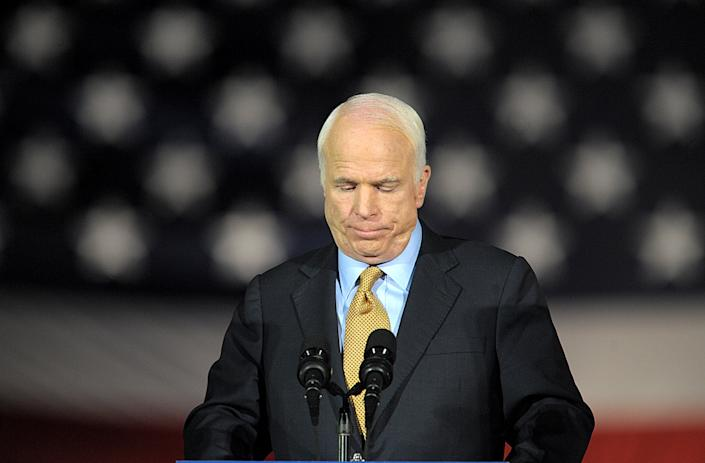 John McCain looks down while standing at a podium