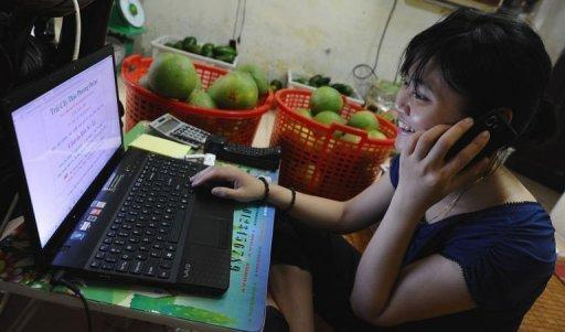 Thao Phuong, an employee of Hanoi Posts Company, works on her laptop as a part-time e-trader selling fruit in Hanoi. Vietnam's young, tech-savvy population is turning to the Internet to break out of an economic system stifled by decades of communist rule, leading to a boom in e-commerce