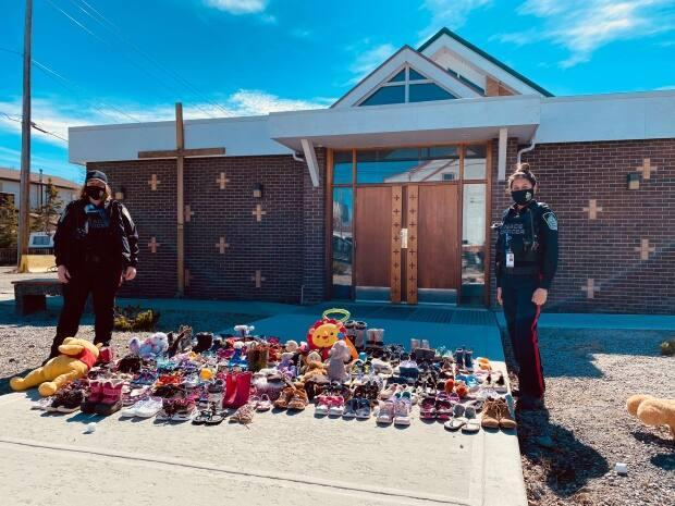 Two peace officers, who came to lay shoes at a makeshift memorial outside a Yellowknife church, pause for a photo. People across the North shared their grief publicly after learning about the Tk'emlúps te Secwépemc First Nation's discovery of the remains of 215 Indigenous children at the former Kamloops Indian Residential School. (Eden Maury/CBC - image credit)