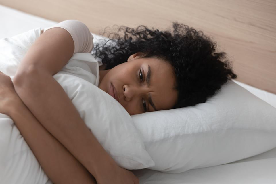 Sad depressed african american young woman hugging pillow lying in bed alone, upset frustrated black lady feeling lonely anxious suffer from insomnia trying to sleep thinking of problem in bedroom