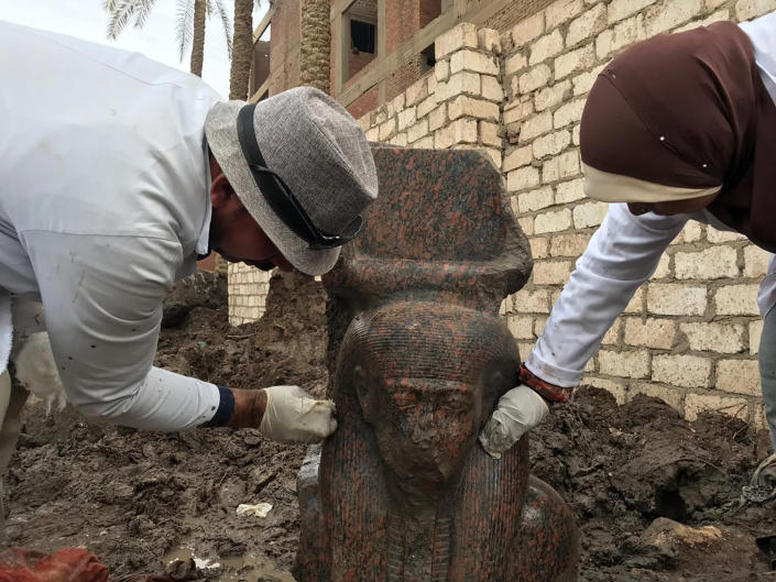 In this Wednesday, Dec. 11, 2019, photo released by Egyptian Ministry of Antiquities, archaeology workers clean a small pink granite statue of Ramses II, near the ancient pyramids of Giza, Egypt. Archeologists in Egypt unveiled two new discoveries, the rare statue of Ramses II, one of the country's most famous pharaohs, and a diminutive ancient sphinx that was found in the southern desert province of Minya. (Egyptian Ministry of Antiquities via AP)