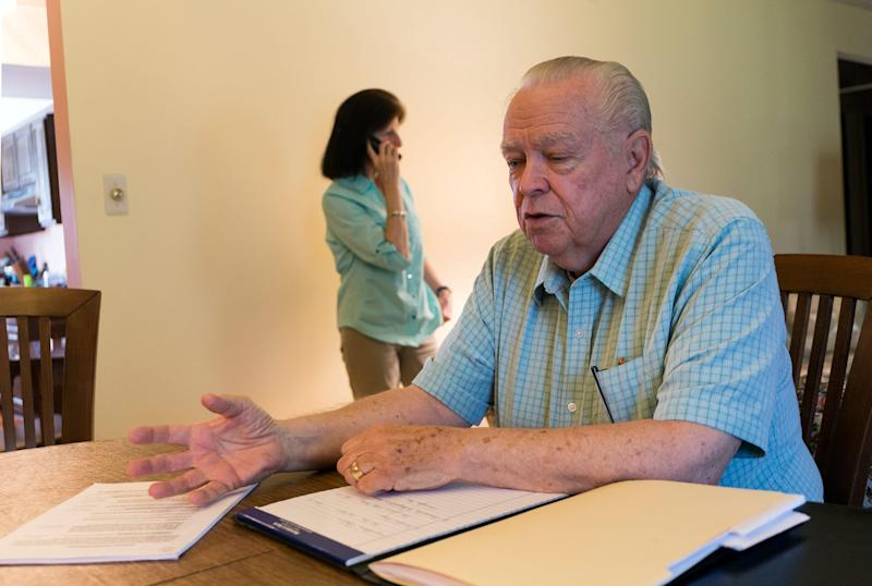 "Robert Allison, 74, speaks to the Detroit Free Press about his troubles after getting caught in a ""Timeshare Exit Trap."" He filed a complaint with the Better Business Bureau in St. Louis after timeshare relief work wasn't completed. His wife Suzann takes a robocall in the background at their home in Farmington Hills, Tuesday, June 11, 2019."