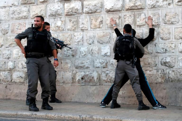 Israeli borderguards search a Palestinian man outside Damascus Gate in Jerusalem's Old City