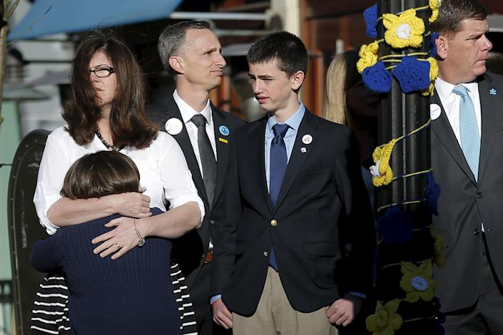 The family of Boston Marathon bombing victim Martin Richard joins Boston Mayor Marty Walsh (R) at a ceremony at the site of the second bomb blast on the second anniversary of the bombings in Boston, Massachusetts April 15, 2015. Martin Richard's mother Denise (top L) hugs her daughter Jane (L) as father Bill (3rd L) and son Henry stand at their side after unveiling the banner for this year's race to be run April 20. REUTERS/Brian Snyder