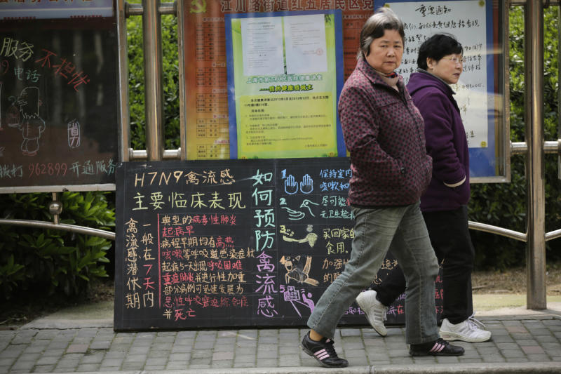 In this April 9, 2013 photo, women walk past a notice on bird flu at a residential area in Minhang district, south of Shanghai, China. After a new and lethal strain of bird flu emerged in Shanghai two weeks ago, the government of China's bustling financial capital responded with live updates on a Twitter-like microblog. It's a starkly different approach than a decade ago, when Chinese officials silenced reporting as a deadly pneumonia later known as SARS killed dozens in the south. (AP Photo/Eugene Hoshiko)