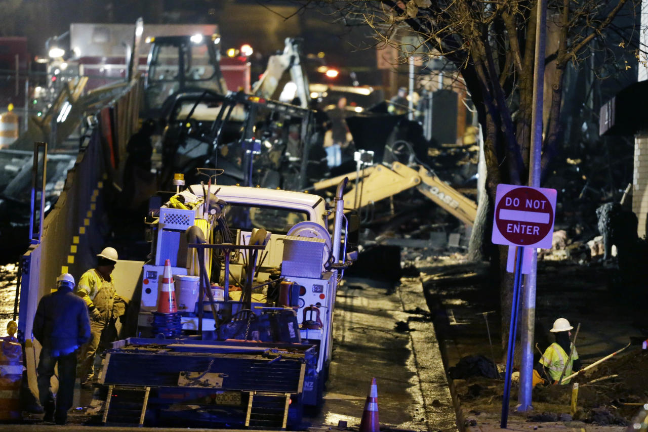 Utility workers repair gas lines near a building that exploded and caught fire in the Plaza shopping district of Kansas City, Mo., Tuesday, Feb. 19, 2013. (AP Photo/Orlin Wagner)