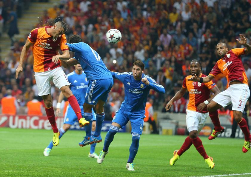 Burak Yilmaz of Galatasaray, left, heads the ball,  during the Champions League Group B soccer match against Real Madrid, in Istanbul, Turkey, Tuesday, Sept. 17, 2013. (AP Photo)