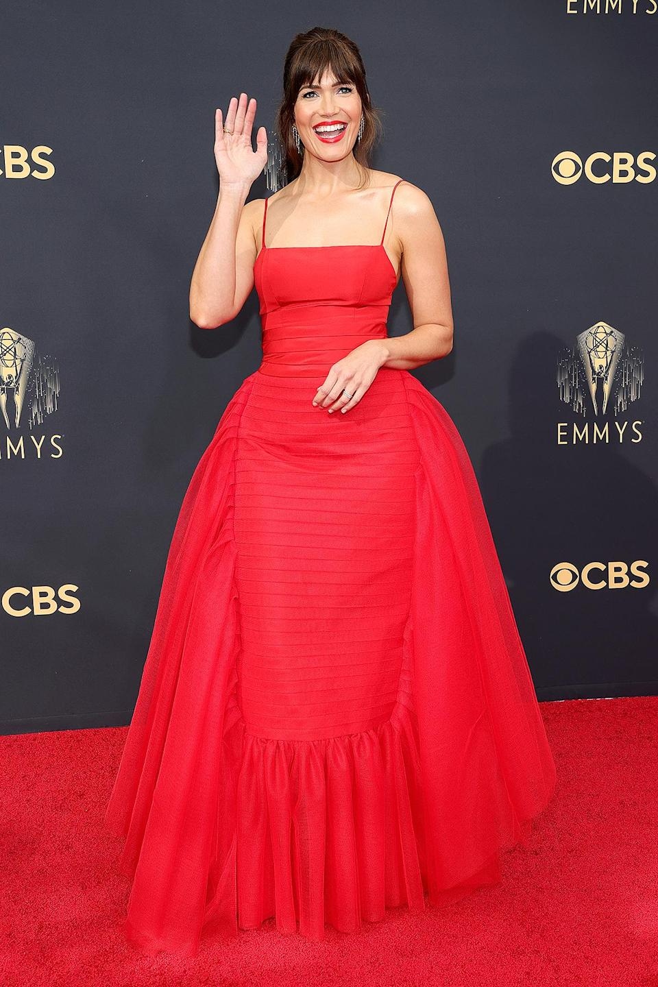 <p>wears a bright red spaghetti-strap gown with ruffled tulle skirt.</p>