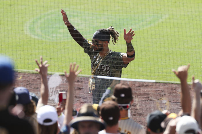 San Diego Padres' Fernando Tatis Jr. waves to fans as he walks off the field wearing an SD medallion following a victory over the Seattle Mariners in a baseball game Sunday, May 23, 2021, in San Diego. (AP Photo/Derrick Tuskan)