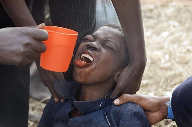 <p>A weak Rwandan Hutu refugee strains to receive water at the Kibumba refugee camp, Aug. 1, 1994, near Goma, Zaire (DRC). Relief organizations and military specialists were scrambling to provide clean drinking water for some 1.2 million refugees within Zaire. (Photo: Jacqueline Larma/AP) </p>