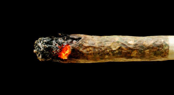 up close photo of a marijuana joint smoldering against a pitch black background