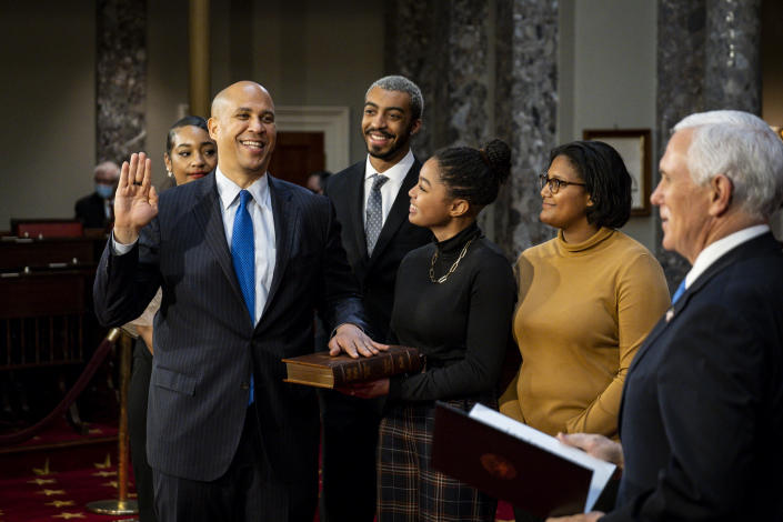 FILE - In this Jan. 3, 2021, file photo, Sen. Cory Booker, D-N.J., raises his hand to take the oath of office from Vice President Mike Pence during a reenactment ceremony in the Old Senate Chamber at the Capitol in Washington. The oath, which normally doesn't attract much attention, has become a common subject in the final days of the Trump presidency, being invoked by members of both parties as they met Wednesday, Jan. 6, 2021 to affirm Biden's win and a pro-Trump mob stormed the U.S. Capitol. (Pete Marovich/The New York Times via AP, Pool, File)
