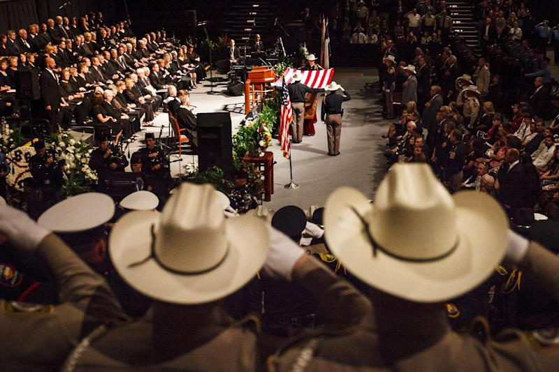 Law enforcement personnel salute Brazos County Precinct 1 Constable Brian Bachmann during the funeral service at Reed Arena on the Texas A&M University Campus, Saturday, Aug. 18, 2012, in College Station, Texas. Bachmann was fatally shot while trying to serve a court summons for being two months behind on rent. (AP Photo/Houston Chronicle, Michael Paulsen) MANDATORY CREDIT: MICHAEL PAULSEN/HOUSTON CHRONICLE
