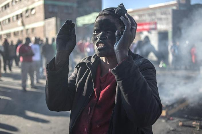 A women covered in soot gestures and shouts towards foreign nationals outside the Jeppies Hostles, in the Jeppestown area of Johannesburg, on April 17, 2015 (AFP Photo/Mujahid Safodien)