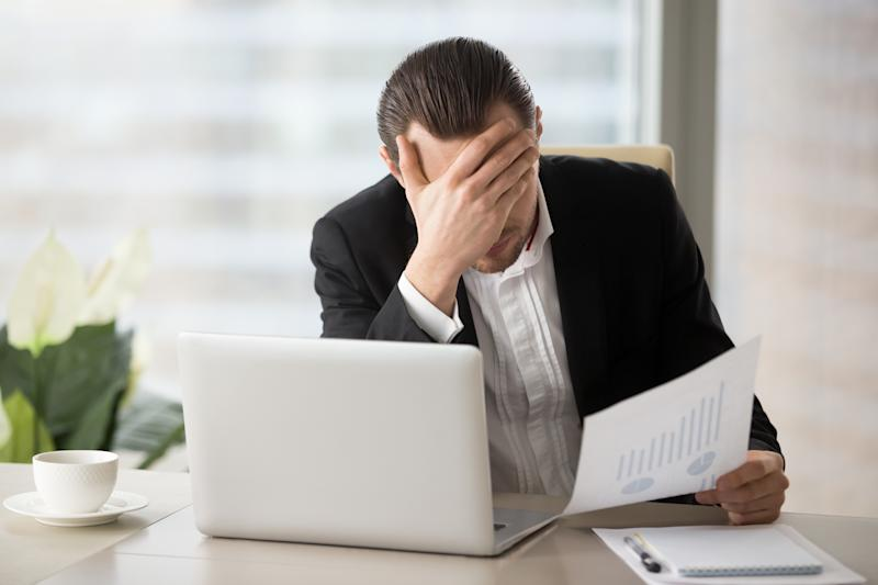 A man in business attire sits at a desk with his hand on his face while looking at a piece of paper.