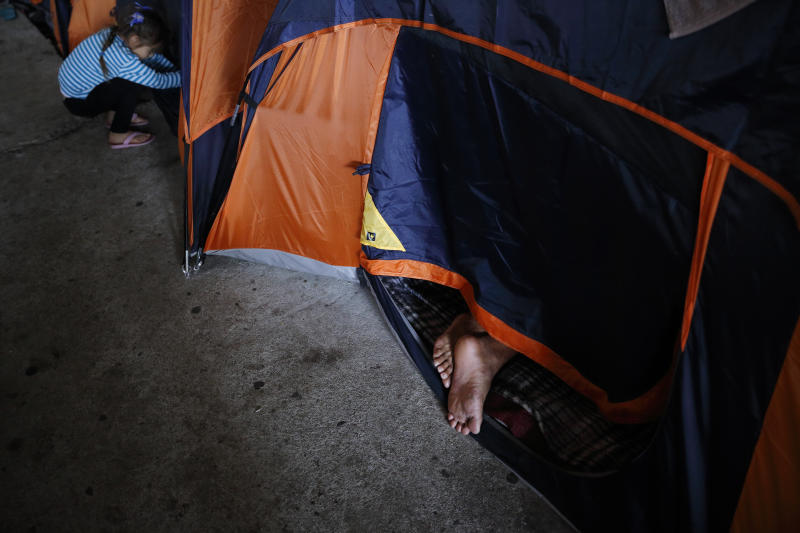 A migrant from the Mexican state of Guerrero, right, sleeps with his feet outside of a tent as he waits at a shelter of mostly Mexican and Central American migrants to begin the process of applying for asylum Friday, April 12, 2019, in Tijuana, Mexico. The Trump administration is asking an appeals court to let it continue returning asylum seekers to Mexico hours before a U.S. judge's order was set to go into effect Friday afternoon reversing the unprecedented change to the U.S. asylum process. (AP Photo/Gregory Bull)