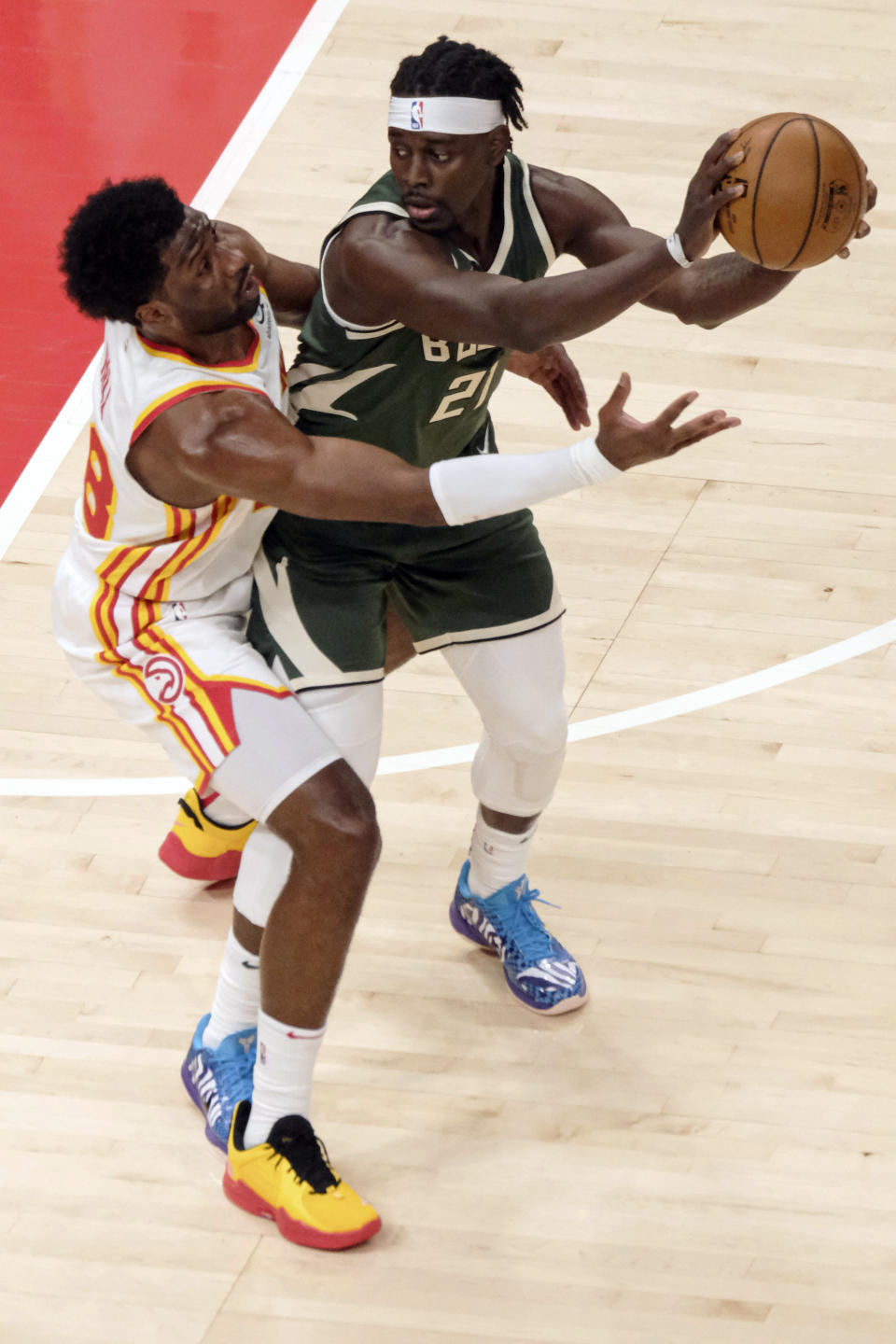 Atlanta Hawks forward Solomon Hill (18) wraps up Milwaukee Bucks guard Jrue Holiday (21) during the first half of an NBA basketball game on Sunday, April 25, 2021, in Atlanta. (AP Photo/Ben Gray)
