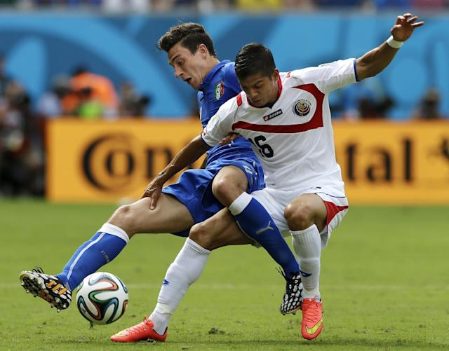 Costa Rica's Cristian Gamboa, right, takes down Italy's Matteo Darmian as they struggle for the ball during the group D World Cup soccer match between Italy and Costa Rica at the Arena Pernambuco in Recife, Brazil, Friday, June 20, 2014. (AP Photo/Ricardo Mazalan)