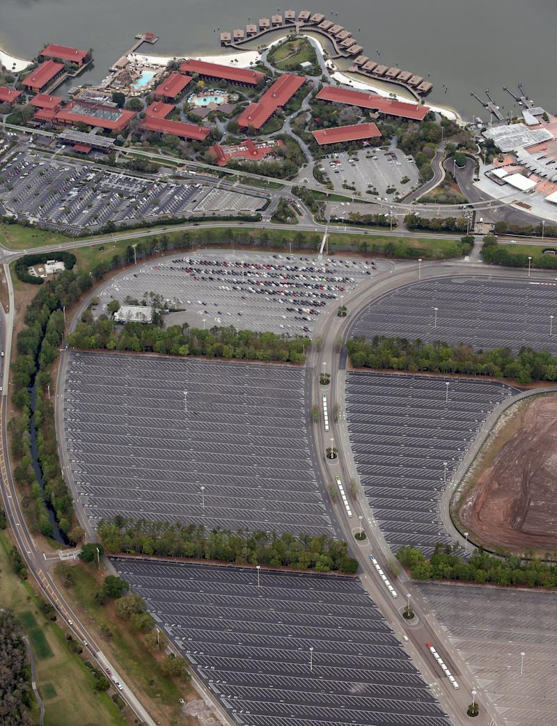 The nearly empty parking lot of Disney's Magic Kingdom theme park after it closed in an effort to combat the spread of coronavirus disease (COVID-19), in an aerial view in Orlando, Florida, U.S. March 16, 2020. At top is Disney's Polynesian Village Resort. REUTERS/Gregg Newton