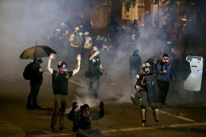 Portland protests return downtown as police use tear gas early Thursday, Aug. 13, 2020. Protesters and police clashed in downtown Portland in a demonstration that lasted into the predawn hours of Thursday, with some in the crowd setting a fire and exploding commercial grade fireworks outside a federal courthouse that's been a target in months of conflict for Oregon's largest city. (Sean Meagher/The Oregonian via AP)