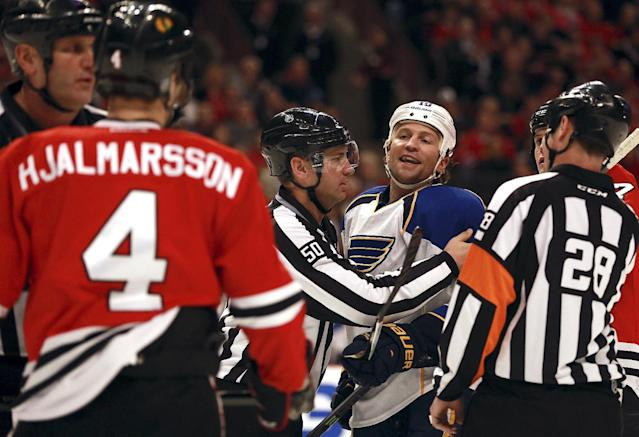Chicago Blackhawks' Niklas Hjalmarsson (4) and St Louis Blues' Brenden Morrow, center right, get separated during the first period of an NHL hockey game in Chicago on Sunday, April 6, 2014. (AP Photo/Charles Cherney)