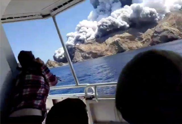 Tourists on a boat react as smoke billows from the eruption.