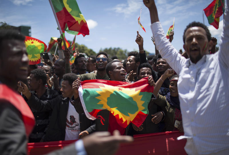 FILE - In this Saturday, Sept. 15, 2018 file photo, a man holds an Oromo Liberation Front (OLF) flag as hundreds of thousands of Ethiopians gathered to welcome returning leaders of the once-banned group in the capital Addis Ababa, Ethiopia. A new report by the rights group Amnesty International issued Friday, May 29, 2020 accuses Ethiopia's security forces of extrajudicial killings and mass detentions in the restive Oromia region even as the country's reformist prime minister was awarded the Nobel Peace Prize. (AP Photo/Mulugeta Ayene, File)