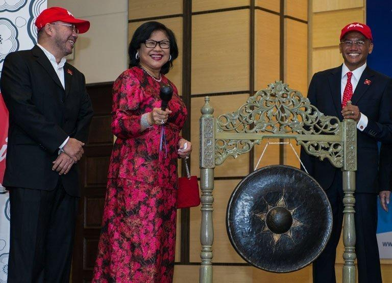 AirAsia X chairman Rafidah Aziz (C) prepares to hit a gong on the firm's listing debut in Kuala Lumpur, July 10, 2013